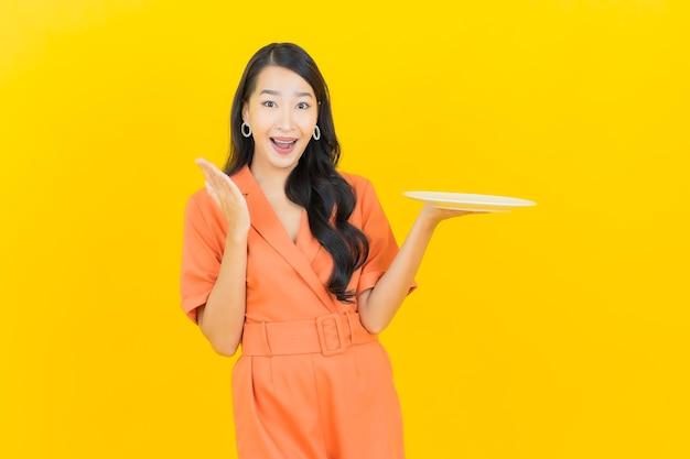 Portret piękna młoda azjatykcia kobieta uśmiech z pustym naczyniem talerz na żółto