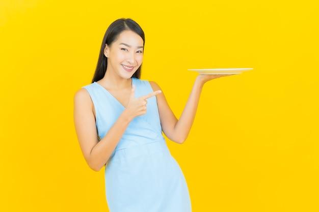 Portret piękna młoda azjatykcia kobieta uśmiech z pustym talerzem naczynia na żółtej ścianie koloru