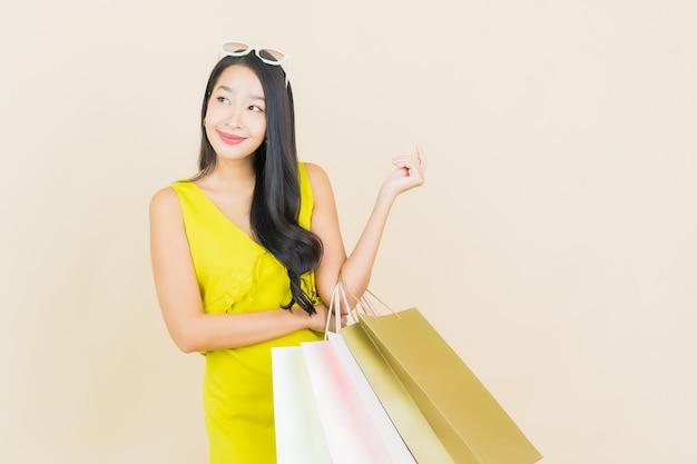 Portret piękna młoda azjatykcia kobieta uśmiech z torbą na zakupy na kolorowej ścianie