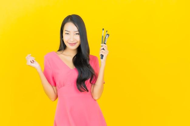 Portret piękna młoda azjatykcia kobieta uśmiecha się kosmetycznym pędzlem do makijażu na żółtej ścianie
