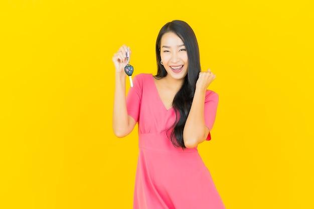 Portret piękna młoda azjatykcia kobieta uśmiecha się z kluczyk na żółtej ścianie