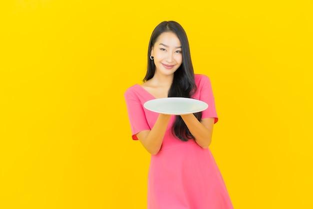 Portret piękna młoda azjatykcia kobieta uśmiecha się z naczynia pusty talerz na żółtej ścianie