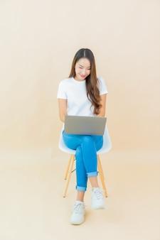 Portret piękna młoda azjatykcia kobieta używa komputerowego laptopa na beżowym tle