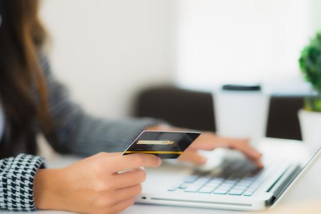 Portret piękna młoda azjatykcia kobieta używa kredytową kartę z laptopem dla online zakupy