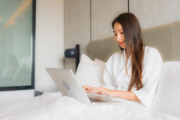 Portret piękna młoda azjatykcia kobieta używa laptop lub komputer w sypialni