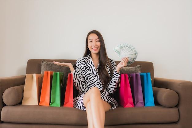 Portret piękna młoda azjatykcia kobieta używa laptopa, inteligentnego telefonu komórkowego lub gotówki na zakupy online na kanapie we wnętrzu salonu