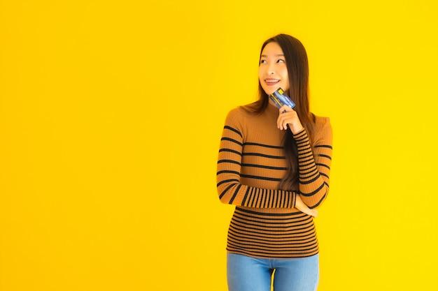 Portret piękna młoda azjatykcia kobieta używa mądrze telefon komórkowego lub telefon komórkowego z kredytową kartą dla online zakupy