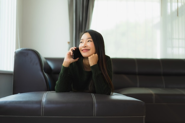 Portret piękna młoda azjatykcia kobieta używa mądrze telefon komórkowego
