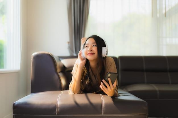Portret piękna młoda azjatykcia kobieta używa smartphone na kanapie z hełmofonami