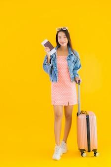 Portret piękna młoda azjatykcia kobieta z bagaż podróży torbą z paszportem i abordaż przepustki biletem