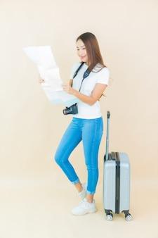 Portret piękna młoda azjatykcia kobieta z bagażem i aparatem gotowym do podróży na beżu