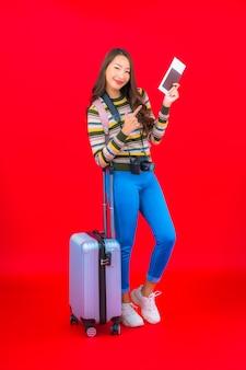 Portret piękna młoda azjatykcia kobieta z bagażem i kartą pokładową na czerwonej ścianie