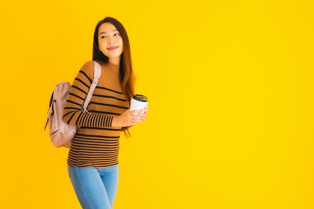Portret piękna młoda azjatykcia kobieta z bagpack i filiżanką w jej ręce
