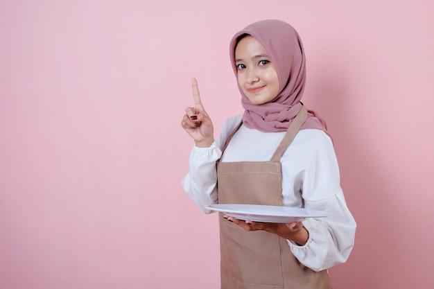 Portret piękna młoda azjatykcia kobieta z białym naczyniem lub talerzem