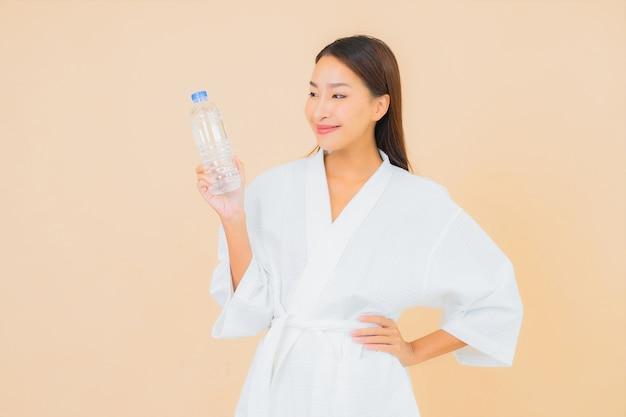 Portret piękna młoda azjatykcia kobieta z butelką wody do picia na beżu