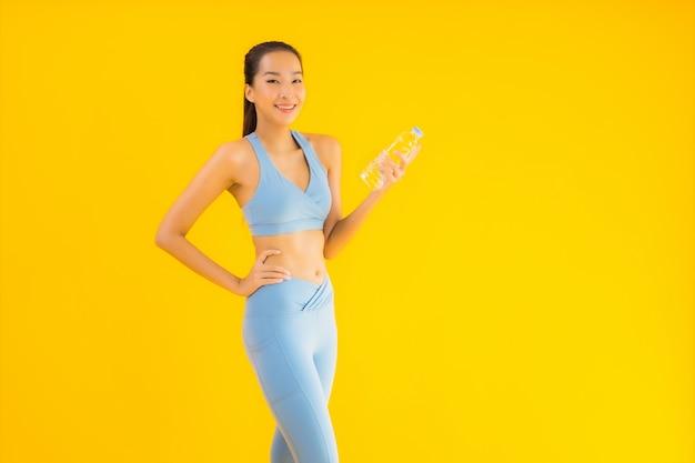 Portret piękna młoda azjatykcia kobieta z butelki wodą na kolorze żółtym