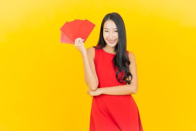 Portret piękna młoda azjatykcia kobieta z chińskiego nowego roku czerwoną kopertą na żółtej ścianie