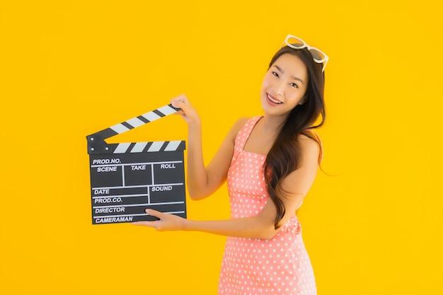Portret piękna młoda azjatykcia kobieta z clapper deską dla kinowego filmu
