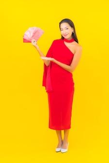 Portret piękna młoda azjatykcia kobieta z czerwoną kopertą list