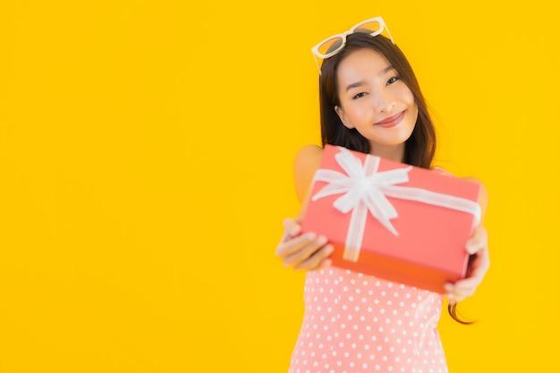 Portret piękna młoda azjatykcia kobieta z czerwonym prezenta pudełkiem