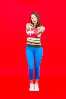 Portret piękna młoda azjatykcia kobieta z czerwonym pudełkiem na czerwonej ścianie