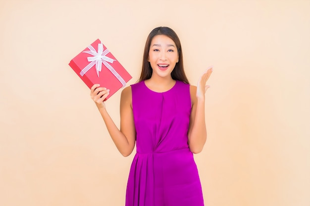 Portret piękna młoda azjatykcia kobieta z czerwonym pudełkiem na kolor na białym tle