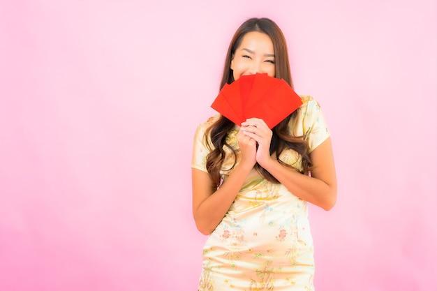 Portret piękna młoda azjatykcia kobieta z czerwonymi kopertami na różowej ścianie
