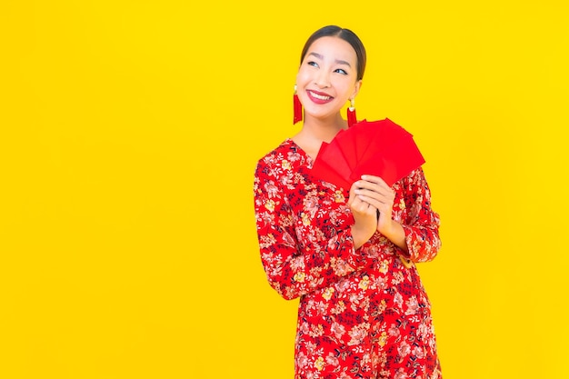 Portret piękna młoda azjatykcia kobieta z czerwonymi kopertami na żółtej ścianie