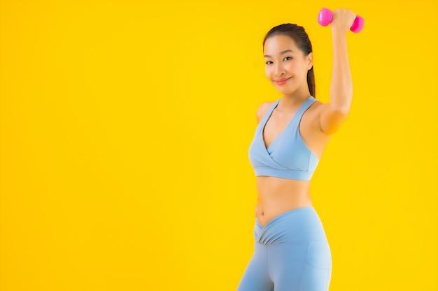 Portret piękna młoda azjatykcia kobieta z dumbbell i sportwear na kolorze żółtym