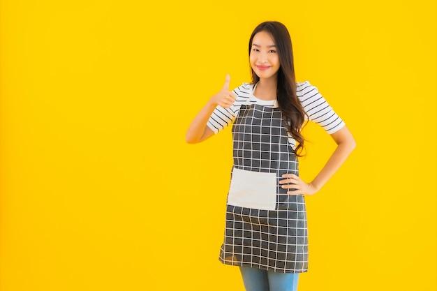 Portret piękna młoda azjatykcia kobieta z fartucha uśmiechem szczęśliwym
