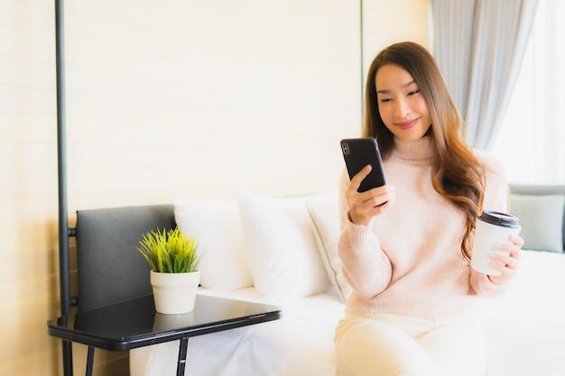 Portret piękna młoda azjatykcia kobieta z filiżanką i telefonem komórkowym na łóżku