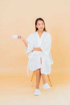 Portret piękna młoda azjatykcia kobieta z filiżanką kawy na beżu