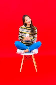 Portret piękna młoda azjatykcia kobieta z filiżanką kawy na czerwonej ścianie na białym tle