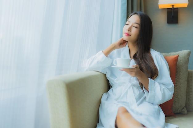 Portret piękna młoda azjatykcia kobieta z filiżanką kawy na kanapie