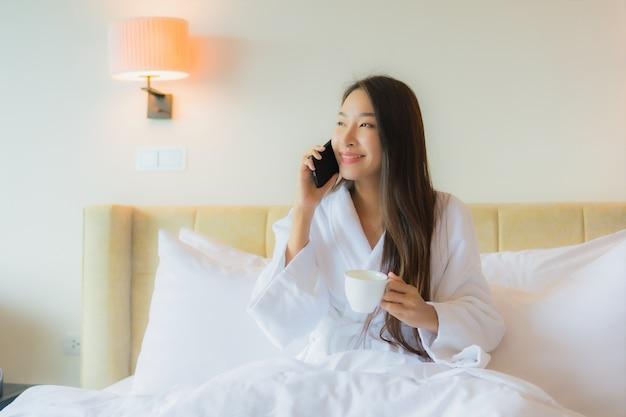 Portret piękna młoda azjatykcia kobieta z filiżanką kawy na łóżku
