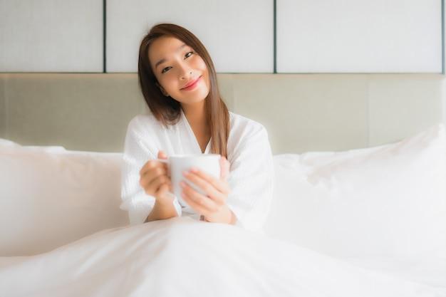 Portret piękna młoda azjatykcia kobieta z filiżanką w sypialni