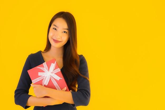 Portret piękna młoda azjatykcia kobieta z giftbox