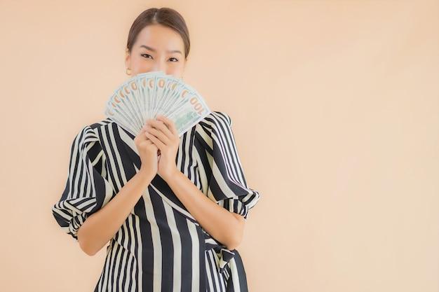 Portret piękna młoda azjatykcia kobieta z gotówką i pieniądze
