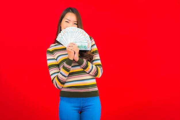 Portret piękna młoda azjatykcia kobieta z gotówką i telefonem komórkowym na czerwonej ścianie
