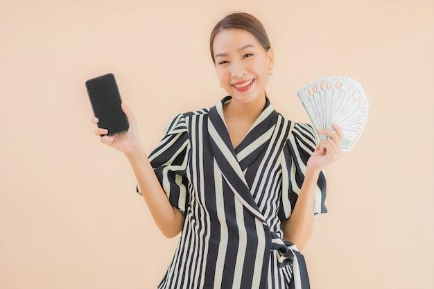 Portret piękna młoda azjatykcia kobieta z gotówkowym i mądrze telefonem komórkowym
