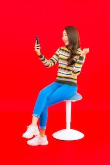 Portret piękna młoda azjatykcia kobieta z inteligentny telefon komórkowy na czerwonej ścianie