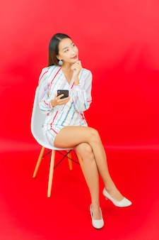 Portret piękna młoda azjatykcia kobieta z inteligentny telefon komórkowy