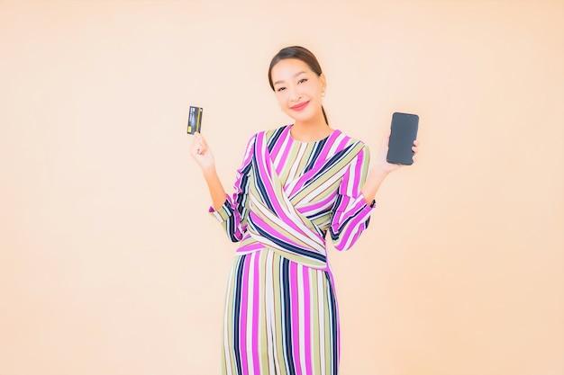 Portret piękna młoda azjatykcia kobieta z inteligentnym telefonem komórkowym i kartą kredytową na kolor