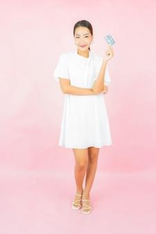 Portret piękna młoda azjatykcia kobieta z kartą kredytową i torbą na zakupy na różowej ścianie