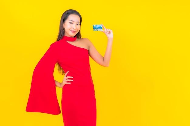 Portret piękna młoda azjatykcia kobieta z kartą kredytową