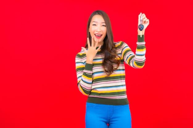 Portret piękna młoda azjatykcia kobieta z kluczyk na czerwonej ścianie na białym tle