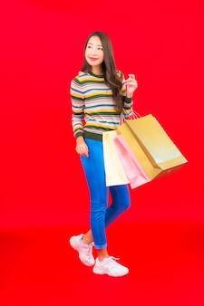 Portret piękna młoda azjatykcia kobieta z kolorową torbą na zakupy na czerwonej ścianie