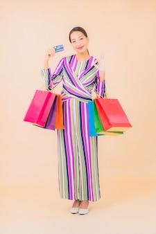 Portret piękna młoda azjatykcia kobieta z kolorową torbą na zakupy na kolor