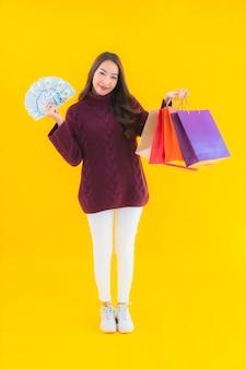 Portret piękna młoda azjatykcia kobieta z kolorową torbą na zakupy