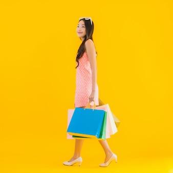 Portret piękna młoda azjatykcia kobieta z kolorowym torba na zakupy